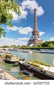 Eiffel tower on the river Seine, Paris, France. Seine with residential boats in the sunlight. Scenic summer view of Seine in Paris. Sunny beautiful Seine postcard.