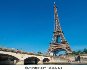 Eiffel Tower on Seine River side. Seeing from boat when float near river bridge.