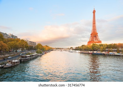Eiffel tower with an orange color at sunset and river seine in Paris, France