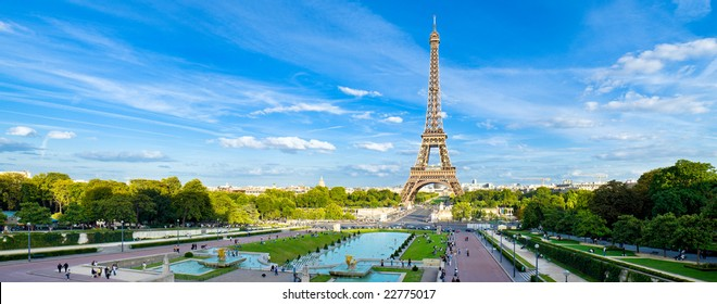 Eiffel Tower panorama, with cloudy blue sky and surrounding park.