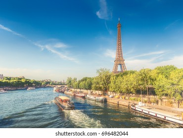 The Eiffel Tower in Paris, France, on a summer day with the river Seine and cruise boat. Daytime skyline. Popular travel destination.