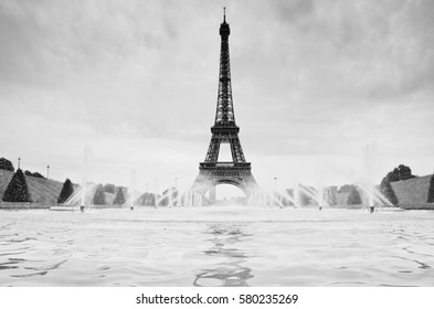 Eiffel tower in Paris in front of fountain with blue sky in background