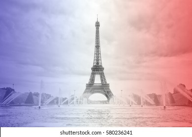 Eiffel tower in Paris in front of fountain with blue sky in background - with colors of France flag