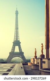 Eiffel Tower in Paris in morning with golden statue in the foreground. Vintage stylized.