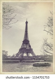 Eiffel Tower in Paris, stylization of an old photo in vintage style. Paris cityscape - your memories from France in retro style. View on Eiffel Tower with a tree at river and a touristic steamboat.