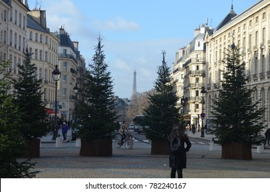 EIFFEL TOWER, PARIS/FRANCE - DECEMBER 2017: View of Eiffel tower from Pantheon, the tower between pines and buildings in a simetrical composition with people around. Paris/France.
