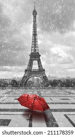 Eiffel tower in the rain with red umbrella. Black and white photo with red element.