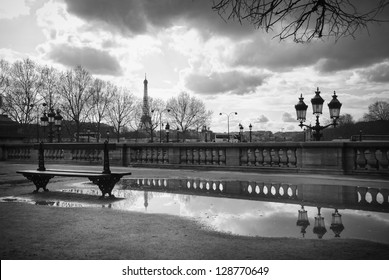 The Eiffel Tower reflecting in a puddle, a bench and an old street lamp in Jardin des Tuileries