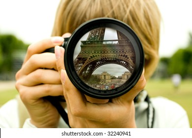 Eiffel tower reflection in camera lens with blurred woman face