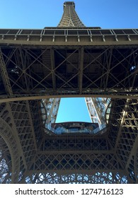 The Eiffel Tower is seen from below the main stage. The windows of the restaurant can be seen. The tower and metal work stand out against a blue sky.