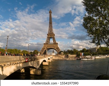Eiffel tower seen in sunny summer morning. In the photo tourists crossing a bridge to see the Iron Lady. Paris - France -  September 2019