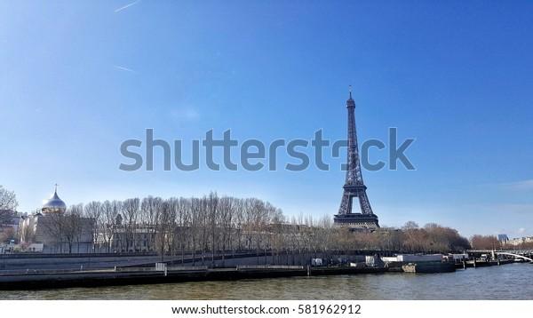 Eiffel tower and Seine river under blue sky