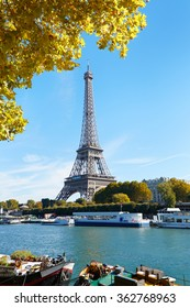 Eiffel tower and Seine river view with yellow autumn tree branches in a sunny day in Paris