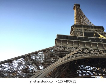 The Eiffel Tower soars into a clear blue sky. Seen from below, a lower leg fills most of the frame, showing the height of the tower.