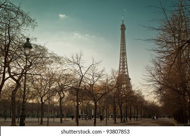 Eiffel tower is standing against  the blue and grey winter sky, with street lamp, leafless trees and alley of Champ de Mars on foreground