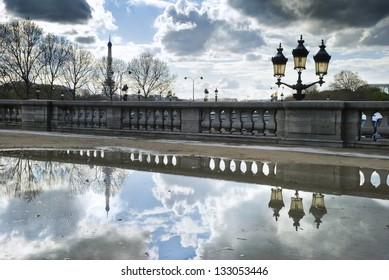 Eiffel Tower and street lamp reflecting in big puddle in Paris, France. This image was taken in Tuileries Garden, close to Place de la Concorde