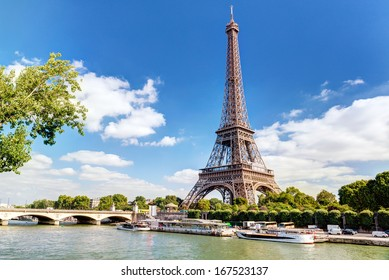 Eiffel tower in summer, Paris, France. Scenic panorama of the river Seine under the blue sky.