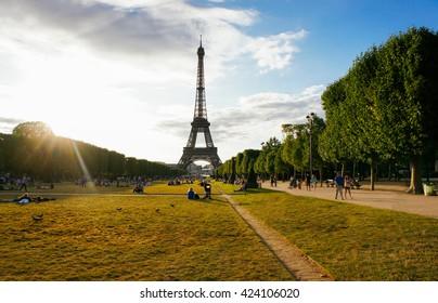 Eiffel tower summer park scene with sunshine beams, Paris. France. Paris park landscape. Famous Eiffel tower with sun beams in Paris, France. Eiffel tower at sunny day Paris, travel landmark concept