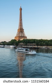 Eiffel Tower at sunset reflecting in the River Seine as boat passes by in Paris France.