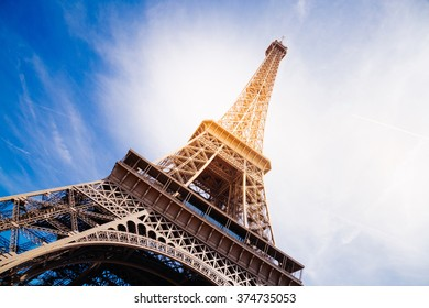 The Eiffel Tower at sunset in summer. Sun effect added