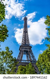 The Eiffel Tower surrounded by tree leaves in Paris, France with white clouds in the background