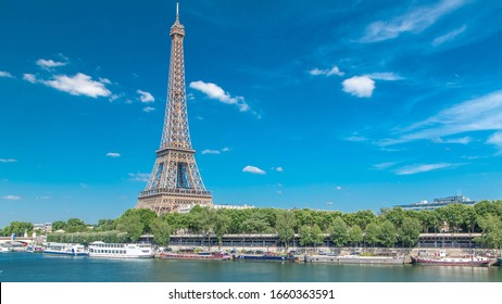 The Eiffel tower timelapse from embankment at the river Seine in Paris. Ship and boats on river at sunny summer day