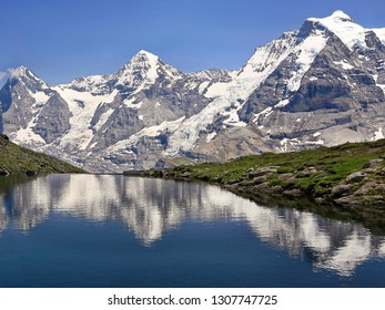 Eiger, Monch and Jungfrau mountains reflected in Grauseewli Lake, Switzerland Alps