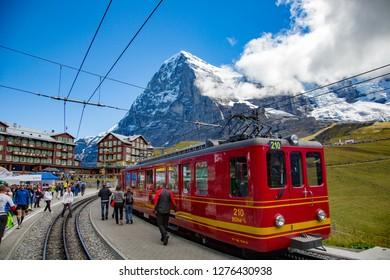 Eiger, Switzerland - 9/8/2014:  A red swis rail train car and the Eiger mountain in the village of Kline Scheidegg, switzerland