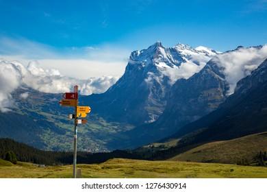 Eiger, Switzerland - 9/8/2014:  A trail sign at Klein Schendegg, Grindelwald and Wetterhorn mountgain are in background.