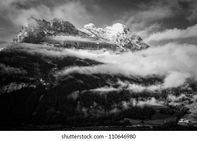 The Eiger Switzerland with lots of levels of cloud in black and white.