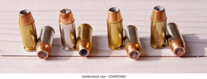 Eight 40 caliber hollow point lined up on a white wooden back ground, the bullets have different cases, some silver and the other brass