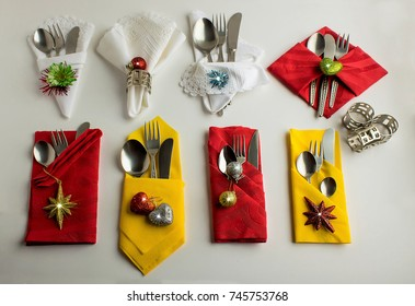 Eight Christmas cloth and paper napkins designed in different shapes with Christmas ornament on the white table.Three metal napkin rings at near napkins and cutlery knife set in napkins.