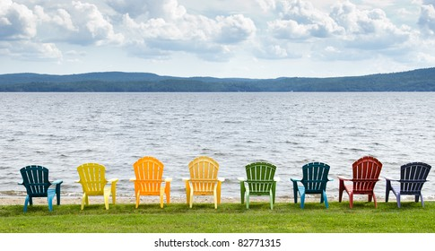 adirondack chairs on beach. Eight Colorful Adirondack Chairs Lined Up On The Beach Looking Out Lake, Mountains 5