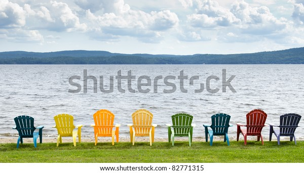 Eight colorful Adirondack chairs lined up on the beach looking out on the lake, mountains and clouds.