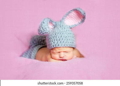 Eight day old smiling newborn baby boy wearing bunny ears and a bunny tail diaper cover. He is sleeping on his stomach pink background