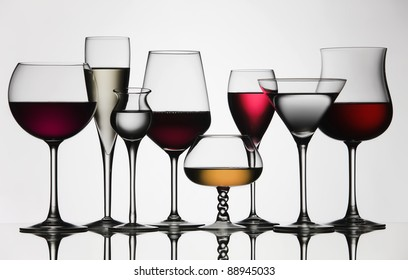 Eight difference glasses of wine and spirit, on a mirror and white background.