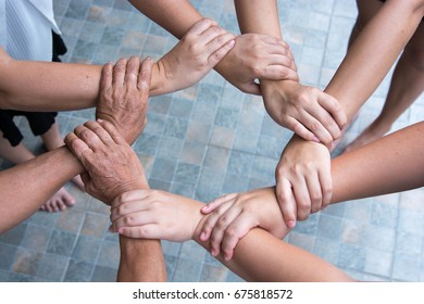 Eight female hands of four woman, from different generations, forming into circle of togetherness. Family concept.