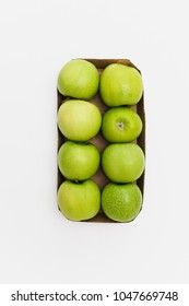 Eight fresh, ripe green yellow Golden Delicious or Granny smith apples neatly packed in supermarket carboard box packaging one lying upside down, all others sideways