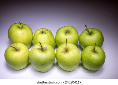 Eight green apples painted with light