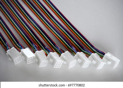 Eight harnesses with colorful wires and white plastic connectors