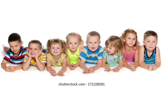 Eight joyful children are lying on the floor on a white background