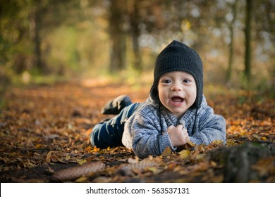 Eight month baby boy laying on belly in autumn forest, smiling with first teeth and looking at viewer