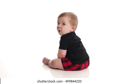 An eight month old baby boy sitting on a white, seamless background. He is looking over his shoulder and making a funny expression with his face.