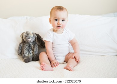 Eight month old baby boy in white onesie poses for monthly portrait