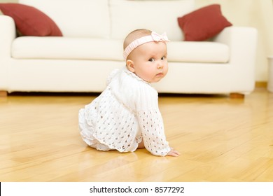 Eight month old baby girl seated on a hardwood floor and turn to the camera. Rear view