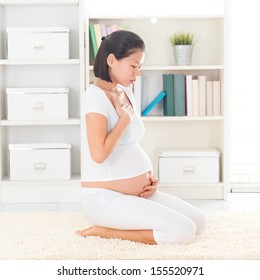 Eight months pregnant Asian woman with nausea at home.