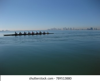 Eight person rowing boat in silhouette on a clear sunny day in Miami Florida. Glassy water.