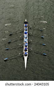 An eight person shell with a coxswain in the middle of a rowing race