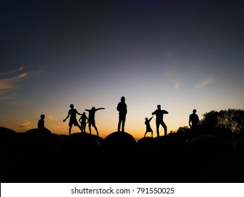 Eight silhouettes standing atop hay bales for a beautiful mid-western sunset. All with varying poses to enhance the variety of the picture. This will be sure to catch peoples attention wherever it i