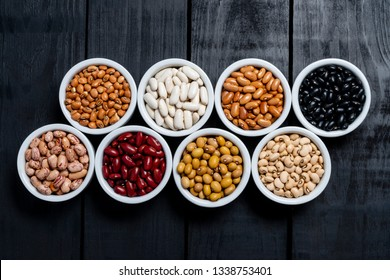 Eight varieties of beans inside white pot on black background.